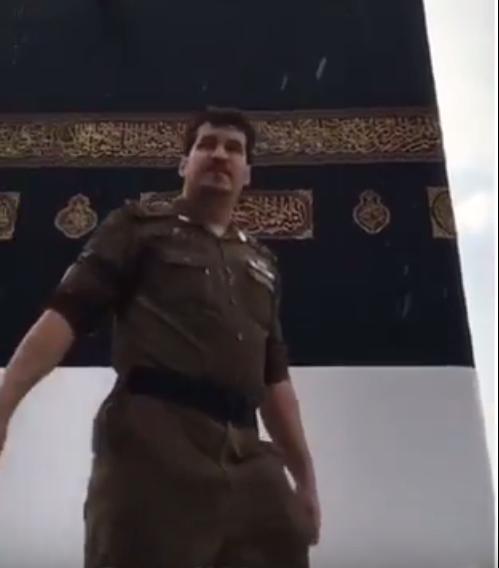 رجل أمن لم تمنعه أمطار مكة من مراقبة حركة الطواف وتوجيه المعتمرين بالحرم